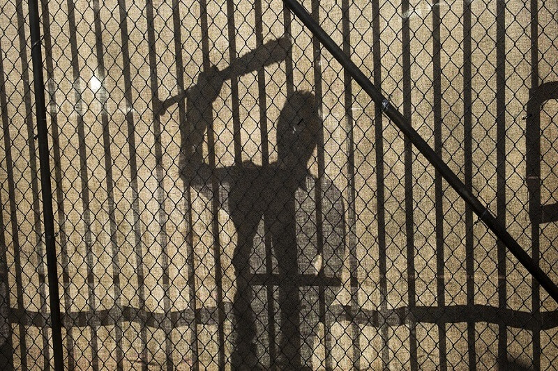 A silhouette of Negan at the gates of Alexandria