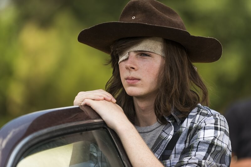 Carl leaning on a car door in The Walking Dead
