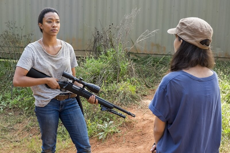 Sasha wielding a sniper rifle talking to Rosita